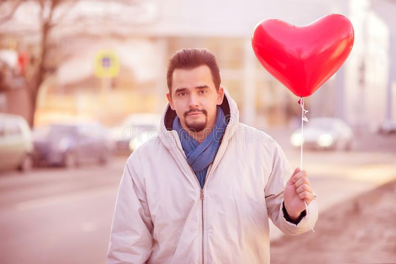 Urban romance: portrait of a smiling handsome bearded man standing in a city street with air balloon shaped as red heart. Toned royalty free stock photos