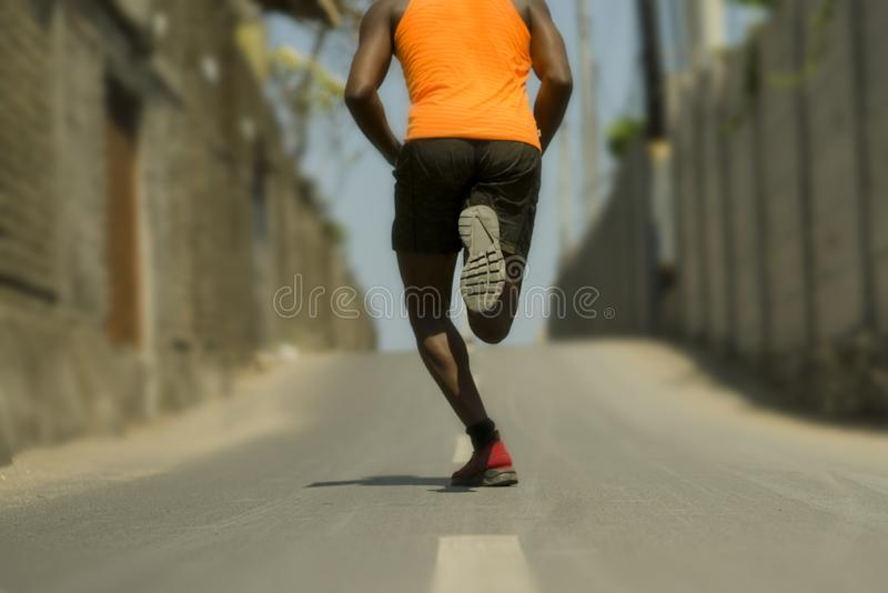 Back view of athletic black African American professional sport man running training hard outdoors on asphalt road during jogging. Urban runner workout . Back royalty free stock images