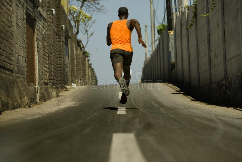Back view of athletic black African American professional sport man running training hard outdoors on asphalt road during jogging. Urban runner workout . Back royalty free stock photos