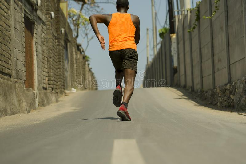 Back view of athletic black afro American professional sport man running training hard outdoors on asphalt road during jogging. Urban runner workout . Back view stock photos