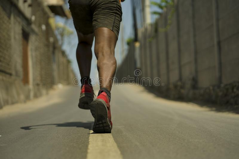 Back view in detail of athletic black African American professional sport man legs and feet in running shoes training outdoors on stock image