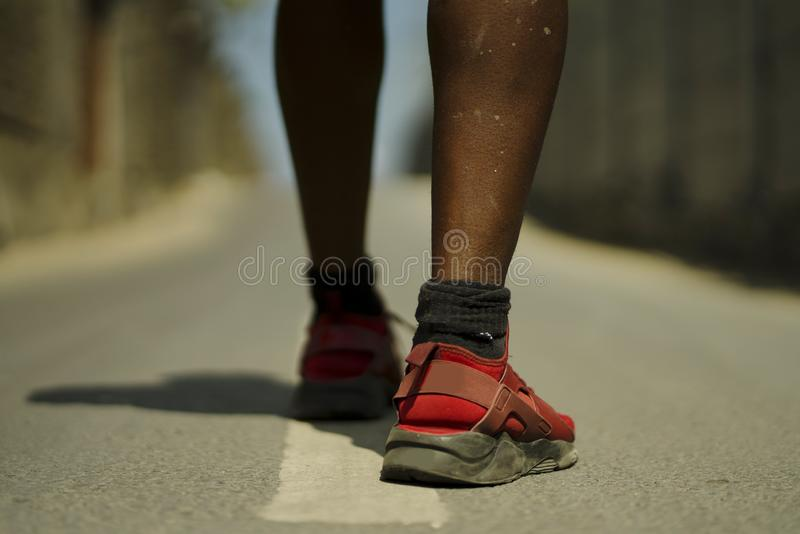 Urban runner workout . Back view in detail of athletic black African American sport man legs and feet in running shoes training. Outdoors on asphalt road during stock image