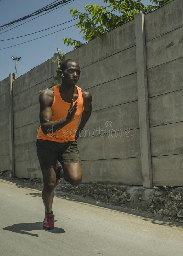 Urban runner workout . Young attractive and athletic black African American man running outdoors on asphalt road training hard. Jogging in sport sacrifice royalty free stock photos