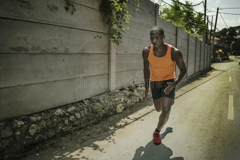 Urban runner workout . Young attractive and athletic black African American man running outdoors on asphalt road training hard. Jogging in sport sacrifice stock photo