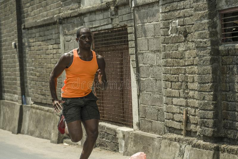Urban runner workout . Young attractive and athletic black African American man running outdoors on asphalt road training hard. Jogging in sport sacrifice stock photography
