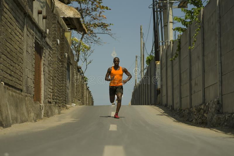 Urban runner workout . Young attractive and athletic black African American man running outdoors on asphalt road training hard. Jogging in sport sacrifice royalty free stock photo