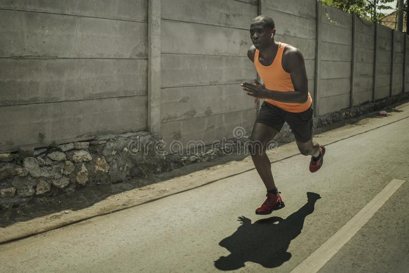 Urban runner workout . Young attractive and athletic black African American man running outdoors on asphalt road training hard. Jogging in sport sacrifice stock images