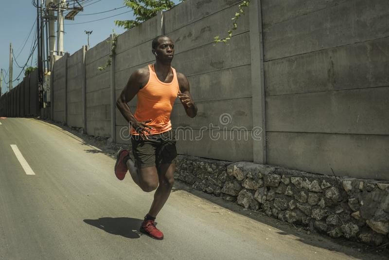 Urban runner workout . Young attractive and athletic black afro American man running outdoors on asphalt road training hard royalty free stock images