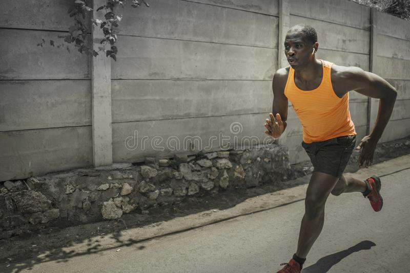 Urban runner workout . Young attractive and athletic black afro American man running outdoors on asphalt road training hard royalty free stock image