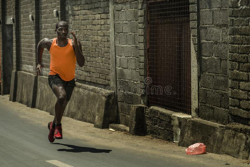 Urban runner workout . Young attractive and athletic black afro American man running outdoors on asphalt road training hard royalty free stock photography