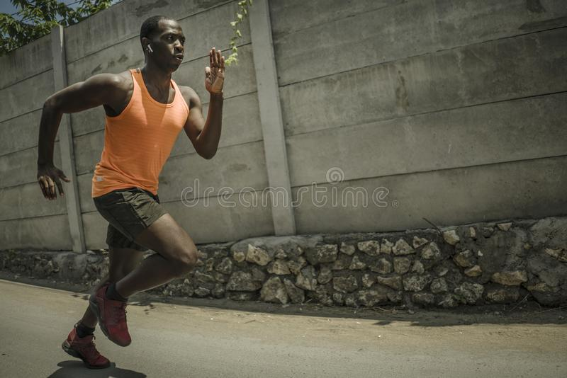 Urban runner workout . Young attractive and athletic black afro American man running outdoors on asphalt road training hard. Jogging in sport sacrifice royalty free stock images