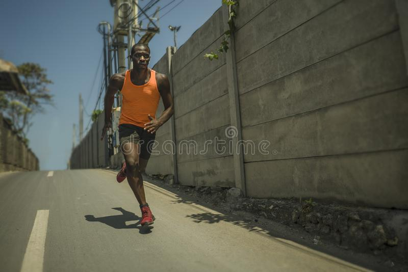Urban runner workout . Young attractive and athletic black afro American man running outdoors on asphalt road training hard. Jogging in sport sacrifice stock images