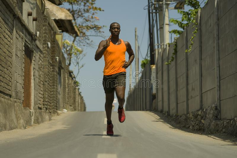 Urban runner workout . Young attractive and athletic black afro American man running outdoors on asphalt road training hard. Jogging in sport sacrifice royalty free stock image