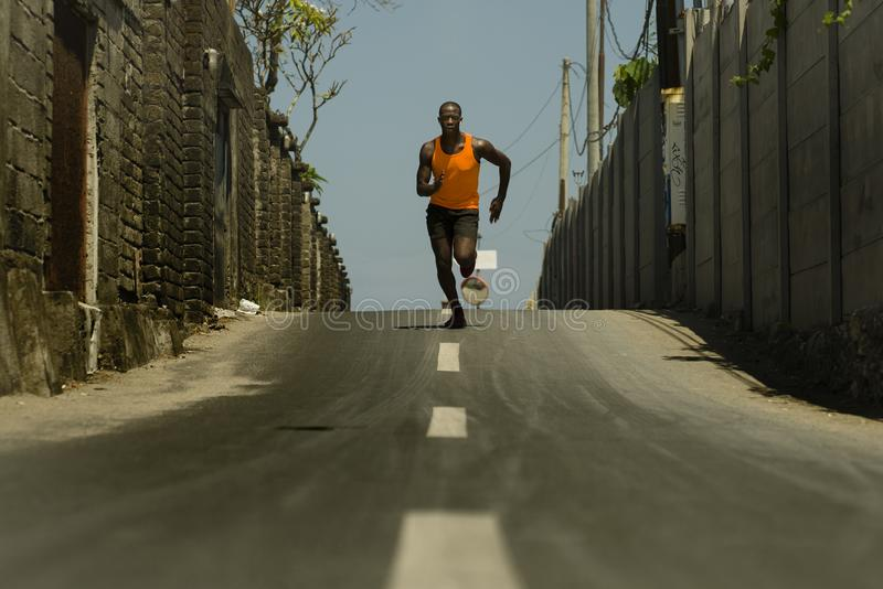 Urban runner workout . Young attractive and athletic black afro American man running outdoors on asphalt road training hard. Jogging in sport sacrifice stock image