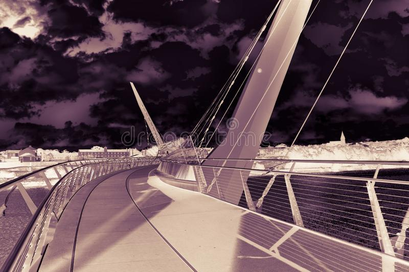 Urban skyline of Derry city also called Londonderry in northern Ireland with the famous. `Peace Bridge` Europe - Northern Ireland - Art Toned image stock photography