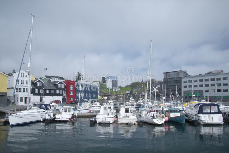Urban skyline with Torshavn Port and distant city with yachts and ships in foreground. stock photography