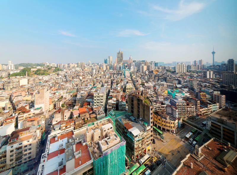Urban skyline of vibrant Macau City under sunny sky, with the famous landmark Macau Tower. And modern skyscrapers in background and crowded old buildings in royalty free stock photos