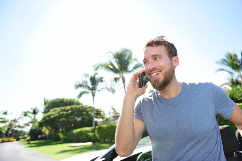Urban smart casual young man talking on smartphone. Urban smart casual young business man talking on smartphone next to his car on a summer day. Happy male adult royalty free stock photography