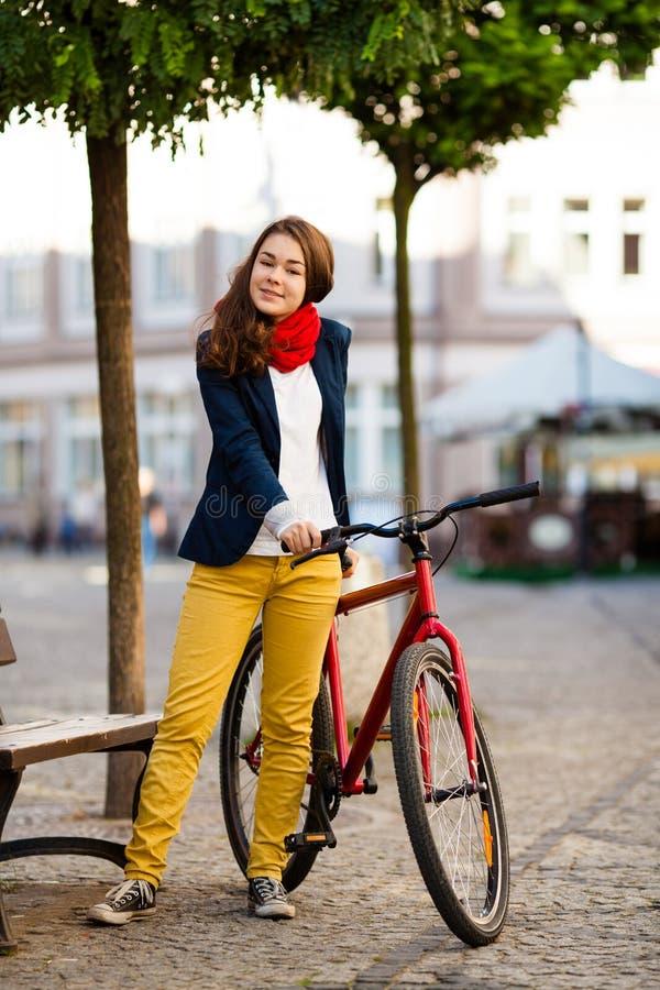 Urban som cyklar - tonårs- flicka och cykel i stad royaltyfri fotografi