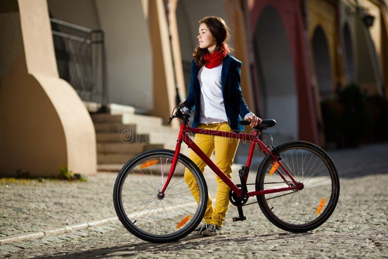 Urban som cyklar - tonårs- flicka och cykel i stad arkivbilder