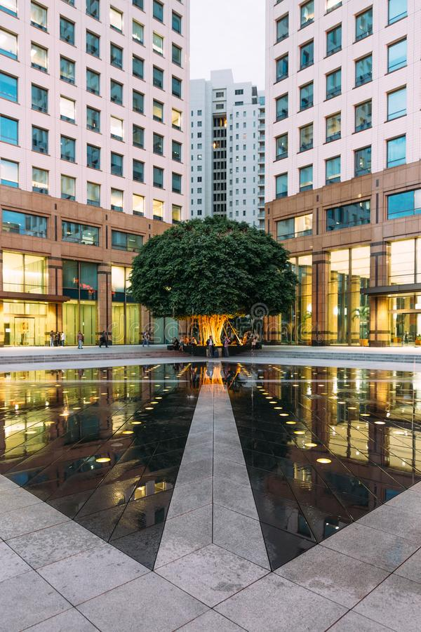 Urban space fountain area with big green tree in the corner with people. This area amid modern office buildings left and right. royalty free stock photography