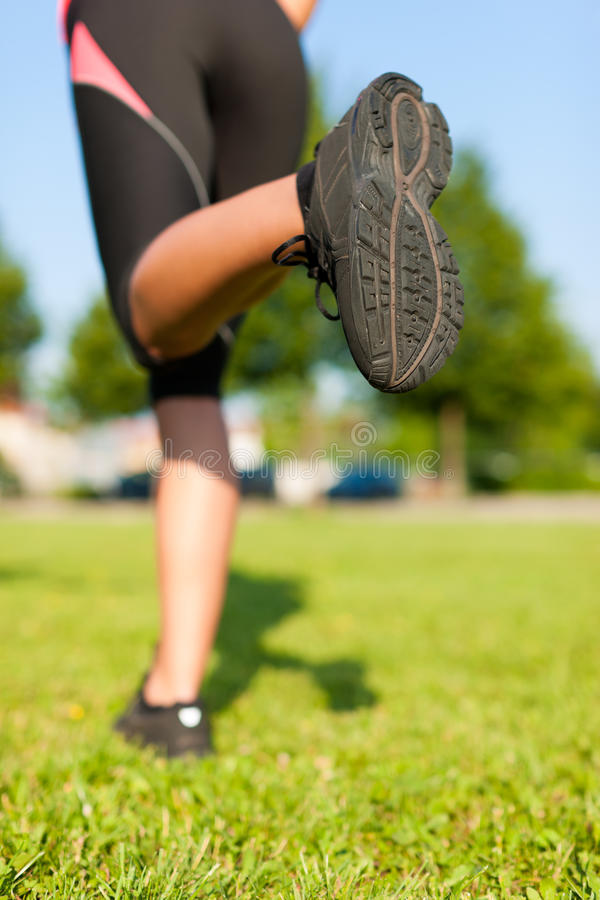 Urban sports - fitness in the city. Sports - young woman jogging for fitness on a beautiful summer day royalty free stock photo