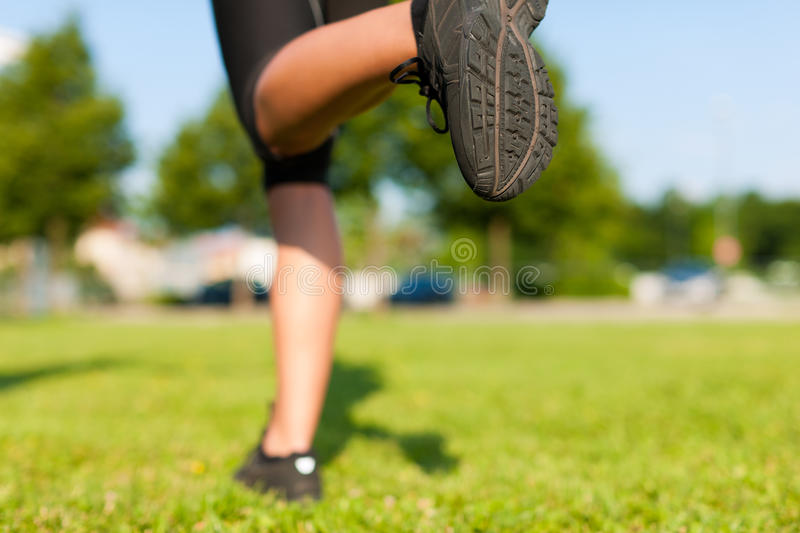 Urban sports - fitness in the city. Sports - young woman jogging for fitness on a beautiful summer day royalty free stock photos