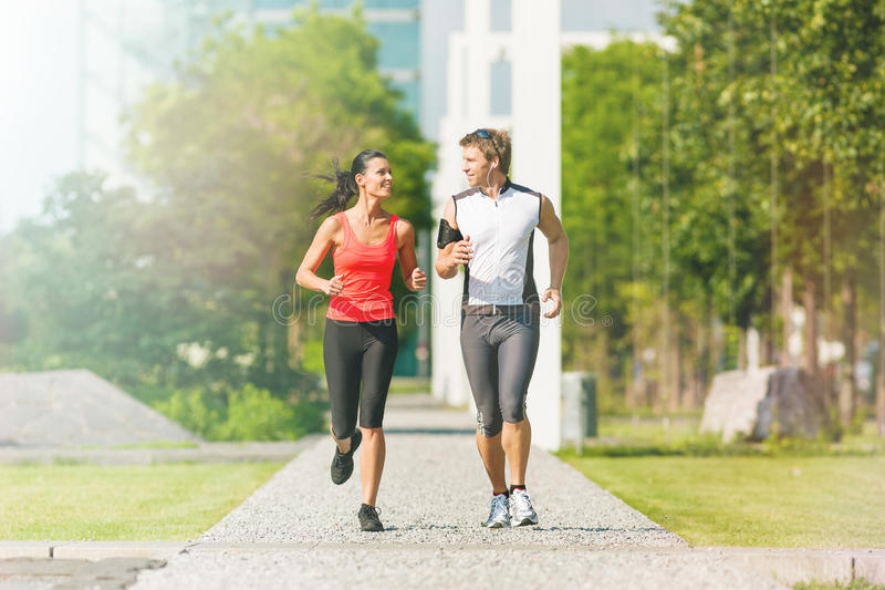 Urban sports - running fitness in the city. Urban sports - couple running or jogging for fitness in the city on beautiful summer day stock image
