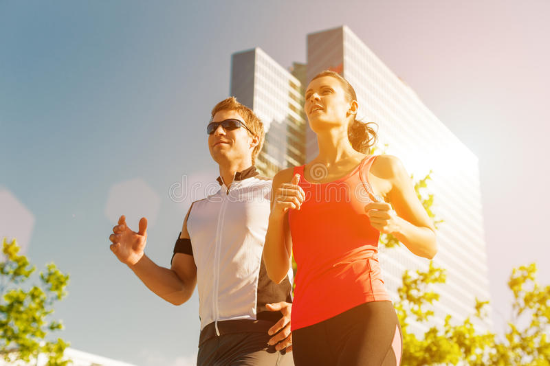 Urban sports - running fitness in the city. Urban sports - couple running or jogging for fitness in the city on beautiful summer day royalty free stock photo