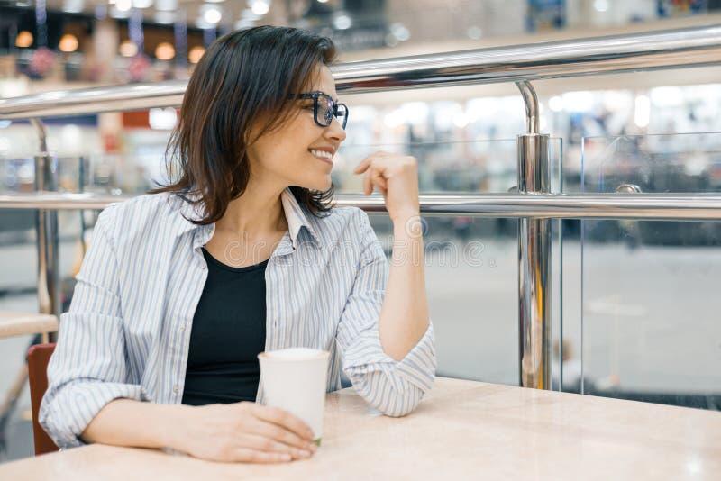 Urban stående av bärande exponeringsglas för mogen kvinna med en kopp kaffe, i att shoppa underhållninggallerian, kvinnligt se i  royaltyfria foton