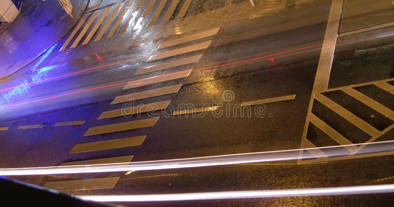 Urban street at night. Angled viewed of urban street at night with traffic light motion blurs and pedestrian crossing stock photography