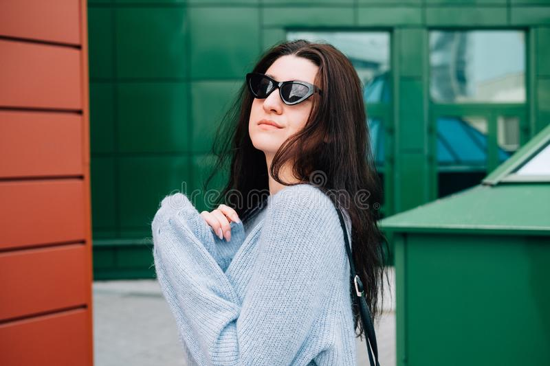 Urban style concept. Close up portrait of fashionable teenage girl in sunglasses posing on city street in summer. Glamour young. Woman wearing stylish clothes royalty free stock images