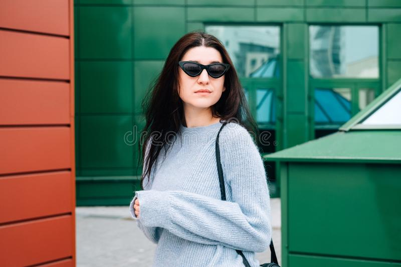 Urban style concept. Close up portrait of fashionable teenage girl in sunglasses posing on city street in summer. Glamour young. Woman wearing stylish clothes stock photo