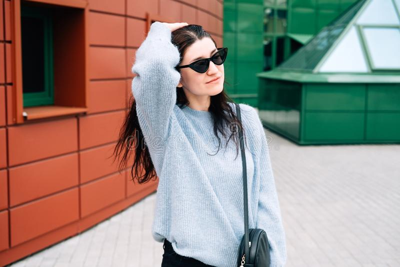 Urban style concept. Close up portrait of fashionable teenage girl in sunglasses posing on city street in summer. Glamour young. Woman wearing stylish clothes stock photos