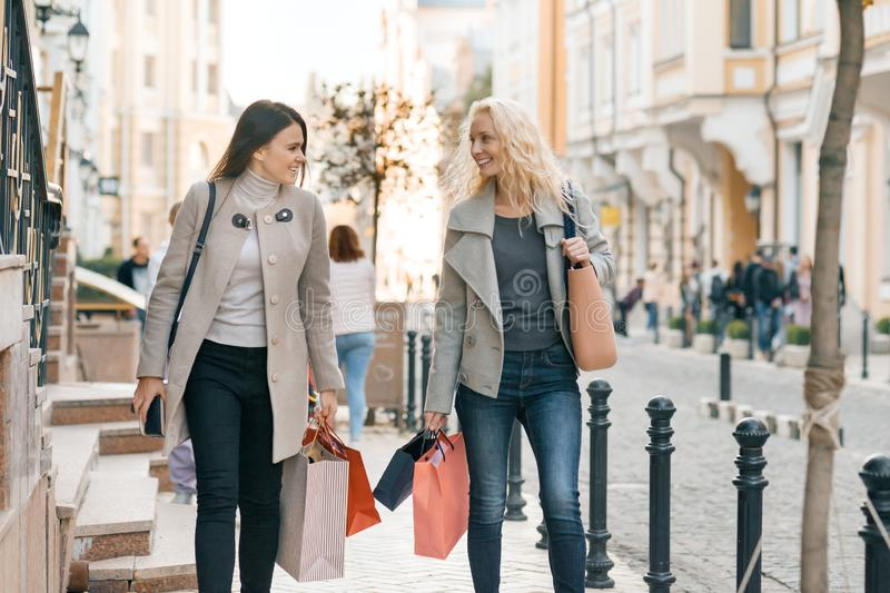 Urban style, two young smiling fashionable women walking along a city street with shopping bags, sunny autumn day, golden hour.  stock photos