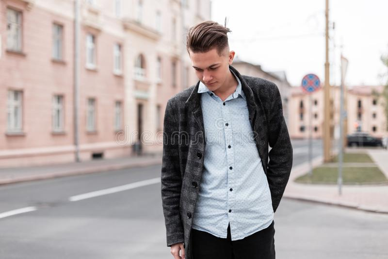 Urban stylish young guy with trendy hairstyle in fashionable elegant clothes  near vintage houses outdoors. Business guy travels. Through the city streets on a royalty free stock photo