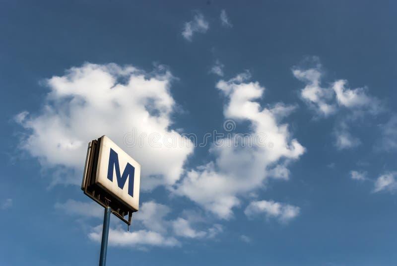 Urban subway sign on blue sky stock photo