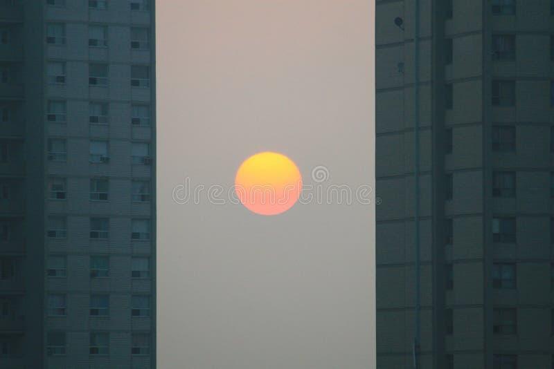 Urban Sunset. The sun sets among the urban landscape stock photo