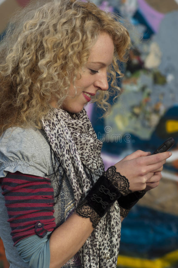 Urban text message 002. Girl texting on cell phone with graffiti in backround royalty free stock photography