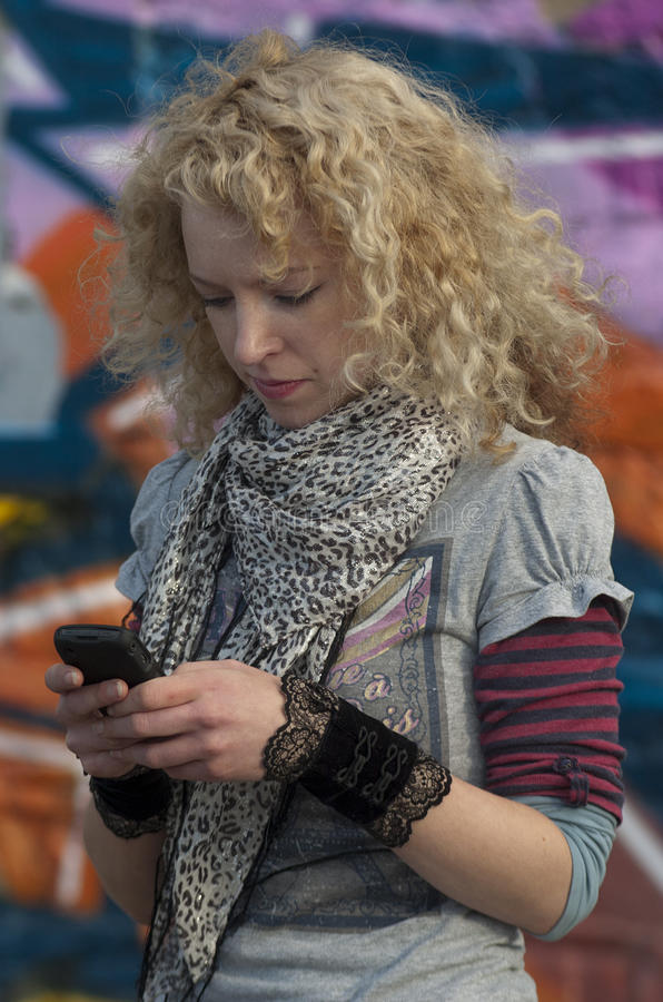 Urban text message. Girl texting on cell phone with graffiti in backround royalty free stock photos