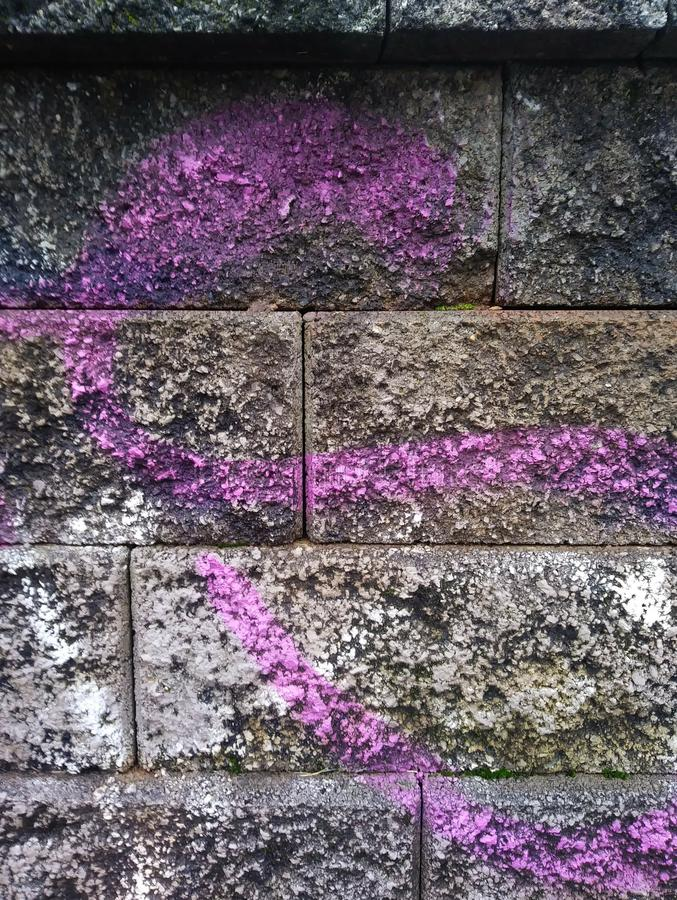 Grungy Urban Wall Surface with Purple Graffiti Scribble. Can be used as background. stock photography