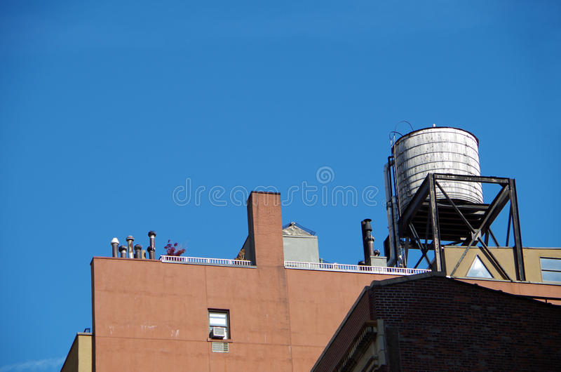 Urban water tower and blue sky. Water tower and buildings seen from street in nyc stock photography