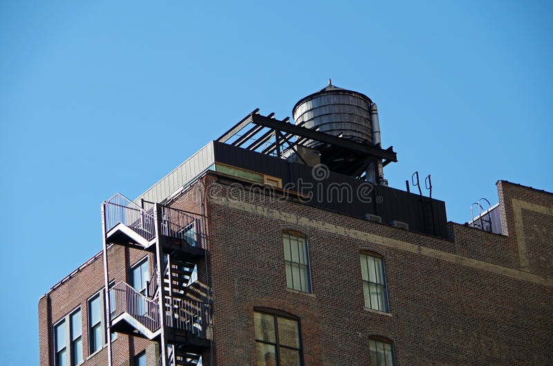 Urban water tower and blue sky. Water tower and buildings seen from street in nyc stock photo