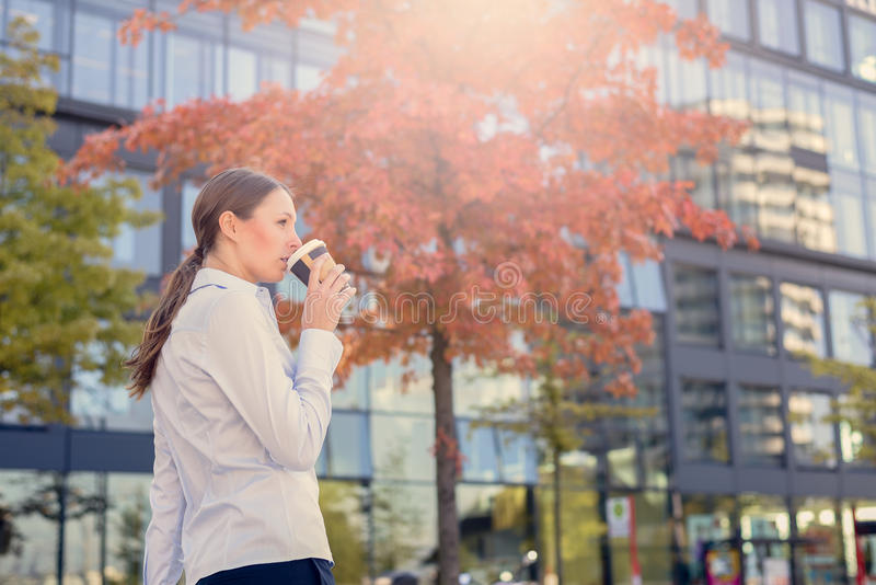 Urban Woman Sipping Coffee in To Go Cup. In Autumn City Environment with Sun Shining in Background royalty free stock photo