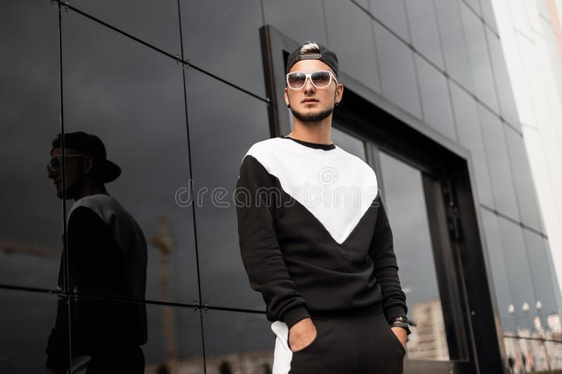 Urban young attractive hipster man with a beard in a black vintage cap in stylish sunglasses in a black fashionable sports suit. Walks through a city. Handsome royalty free stock images
