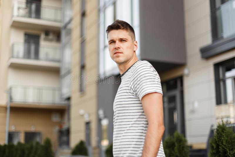 Urban young handsome man fashion model in a fashionable summer t-shirt stands on the street near a modern building. Nice guy walks. Around the city. Stylish new royalty free stock photos