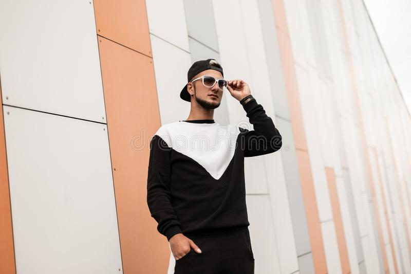 Urban young  hipster man with a beard in a black vintage cap in stylish sunglasses in a black fashionable sports suit walks. Through a city. Attractive guy near stock photo