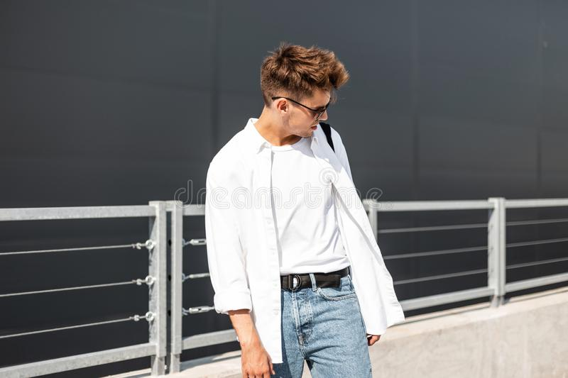 Urban young hipster man in an elegant white shirt in a T-shirt in vintage jeans in trendy sunglasses walks around the city royalty free stock photography