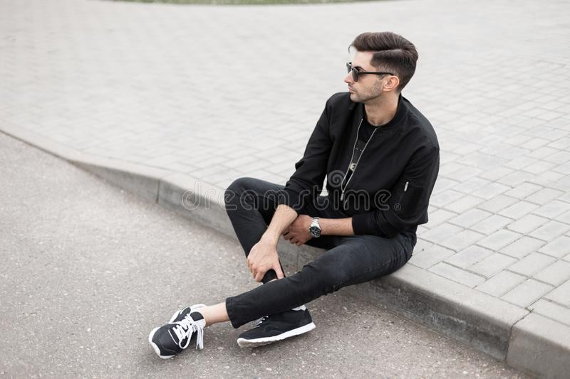 Urban young hipster man in a stylish jacket in black jeans in sneakers in trendy sunglasses is sitting on the sidewalk on a street royalty free stock images