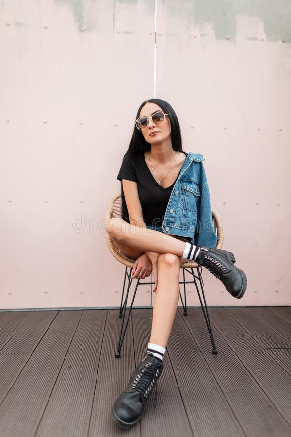 Urban young hipster woman in black leather boots in fashionable jeans clothes in stylish sunglasses posing on a straw chair. Near the pink wall. Trendy girl royalty free stock image
